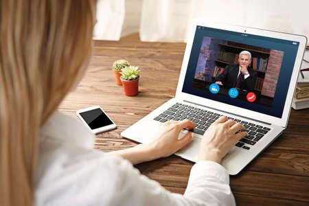 Videoconferencia de mujer con abogado en la computadora portátil. Videollamada y concepto de servicio en línea. Foto de archivo