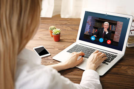 Woman video conferencing with lawyer on laptop. Video call and online service concept. Stok Fotoğraf