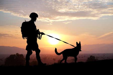 Sylwetki żołnierza i psa na tle zachodu słońca. Koncepcja służby wojskowej.