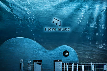 Creative art work concept. Electric guitar on ocean bottom underwater. Text I LOVE MUSIC.