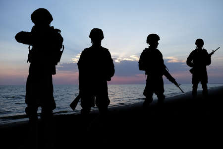 squad: Silhouettes of soldiers on sunset background. Military service concept.