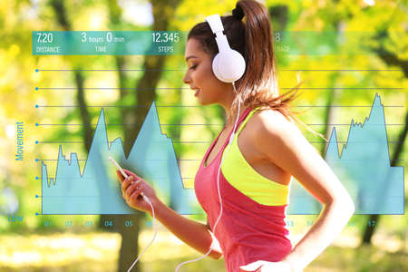 Young woman jogging at park. Graphic of training results. Health care and sport concept. Stock Photo