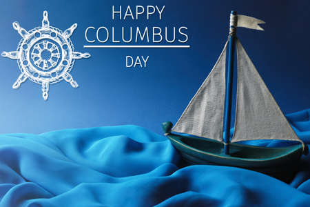 discoverer: Text HAPPY COLUMBUS DAY with wooden boat on blue background. National holiday concept.