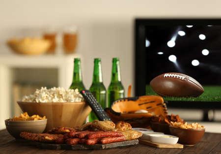 Amerikaans voetbalwedstrijd op televisie thuis kijken. Vrije tijd en vermaakconcept. Stockfoto