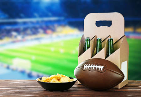 6 pack beer: Beer with snack and ball on wooden table against football field background. Sport and entertainment concept.