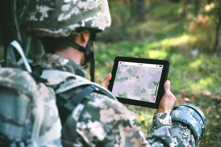 Soldier using map on tablet for orientation at forest Stock fotó - 88596956