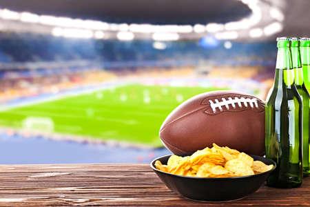 軽食、サッカー フィールドの背景に木製のテーブルの上にボールを持つビール。スポーツやエンターテイメントの概念。