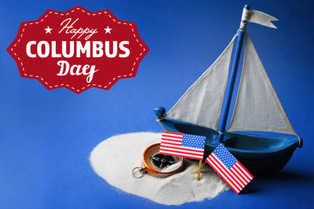 discoverer: Text HAPPY COLUMBUS DAY with wooden boat and compass on blue background. National holiday concept. Foto de archivo