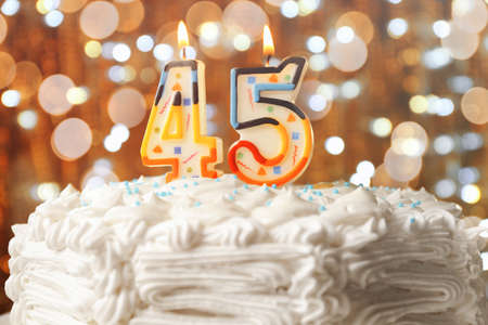 Lighted candles on birthday cake, closeup Stock Photo