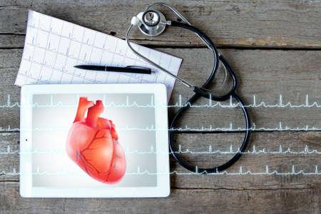 나무 배경에 청진 기와 태블릿. 화면에 마음입니다. 의학 및 현대 기술 개념입니다. 스톡 콘텐츠