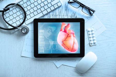 Tablet en toetsenbord op tafel. Hart op scherm. Geneeskunde en moderne technologie concept.