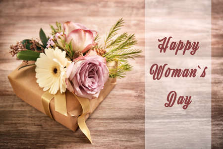 Handcrafted gift box with flowers on wooden background. Text HAPPY WOMANS DAY