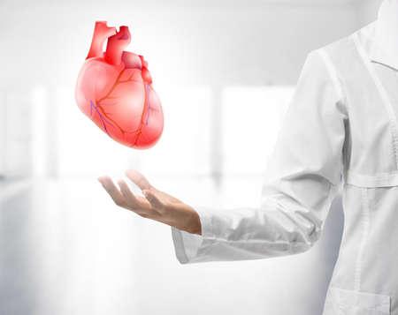 Mano del cardiologo con cuore rosso su sfondo chiaro. Concetto di cardiologia