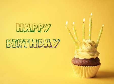 Cupcake with candles and text HAPPY BIRTHDAY on yellow background Stock fotó