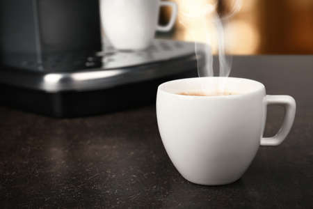 Cup of aromatic coffee on table, closeup