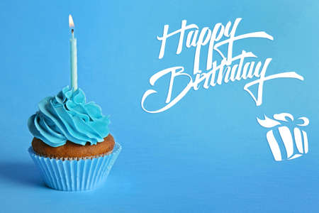 Cupcake with candle and text HAPPY BIRTHDAY on blue background