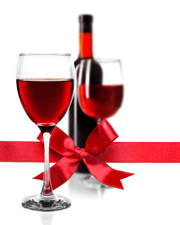 Glass of red wine with festive ribbon bow on white background. Holiday celebration concept.