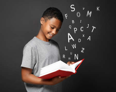 African-American boy with book and alphabet letters on dark background. Speech therapy concept