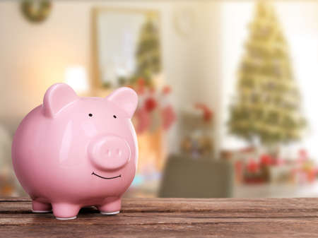 Holiday expenses concept. Piggy bank on wooden table