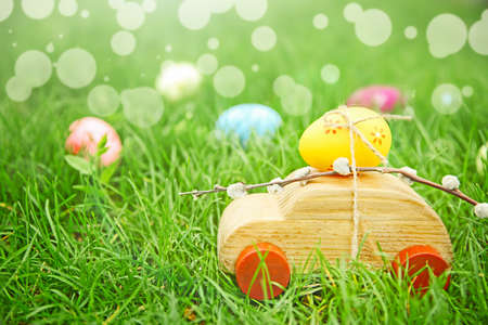 Wooden toy car with Easter egg on green grass Stock Photo