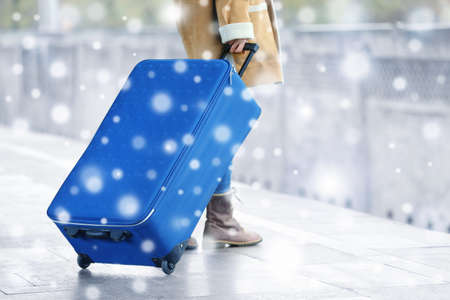 Winter vacation concept. Snowy effect on background. Woman with suitcase outdoor Stock Photo