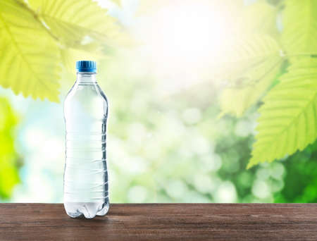 Bottle of clear water on wooden table against nature background