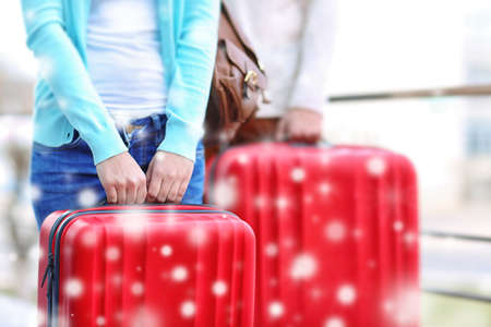 Winter vacation concept. Snowy effect on background. Couple with luggage