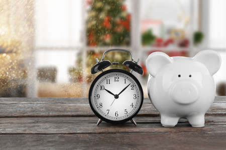 Holiday expenses concept. Piggy bank with alarm clock on wooden table