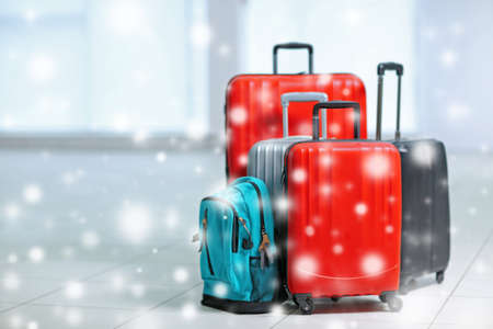 Winter vacation concept. Snowy effect on background. Luggage indoor