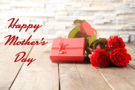 Text HAPPY MOTHERS DAY on background. Gift and roses on wooden table