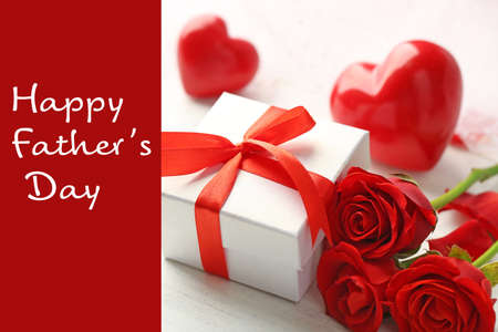 Text HAPPY FATHER'S DAY on background. Gift and roses on table