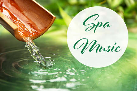 Spa music concept. Pouring water from bamboo stick Stock Photo