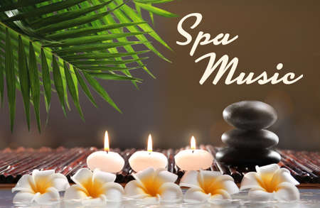 Spa music concept. Stones with candles and flowers on blurred background Stock Photo