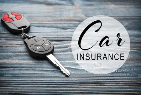 Car insurance concept. Car key with trinket on wooden background Stock Photo