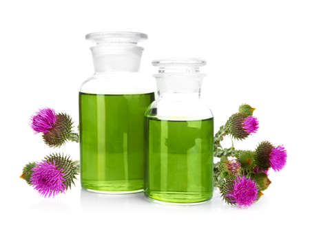 Glass bottles with milk thistle extract and flowers on white background