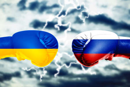 Governments conflict concept. Boxing gloves colored in Ukrainian and Russian flags on sky background Stock Photo