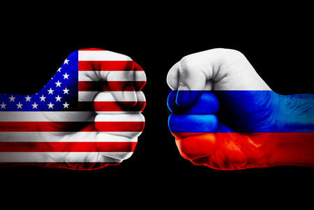 Governments conflict concept. Male fists colored in USA and Russian flags on black background