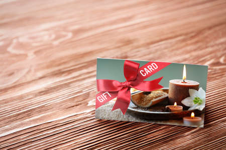 Holiday celebration concept. Spa service gift card on wooden background