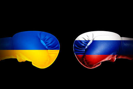 Governments conflict concept. Boxing gloves colored in Ukrainian and Russian flags on black background