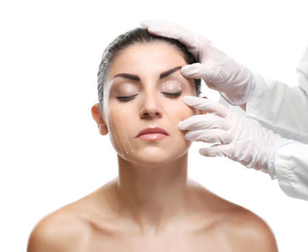 Plastic surgery concept. Doctor examining female face, white background