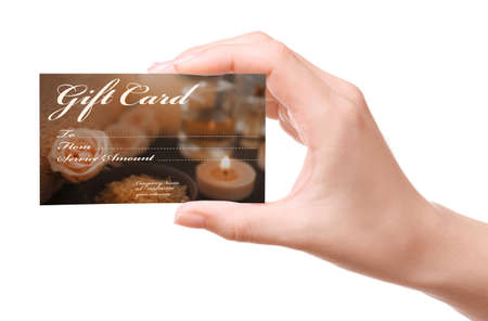 Holiday celebration concept. Female hand with spa service gift card on white background