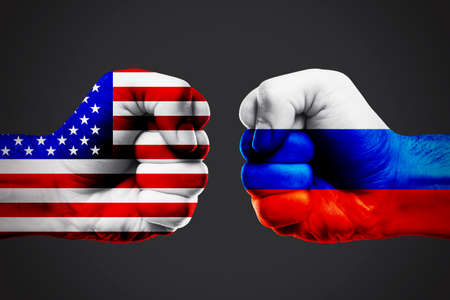 Governments conflict concept. Male fists colored in USA and Russian flags on dark background