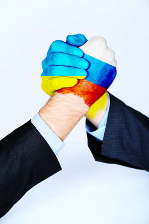 Governments conflict concept. Male hands colored in Ukrainian and Russian flags arm wrestling on light background Stock Photo