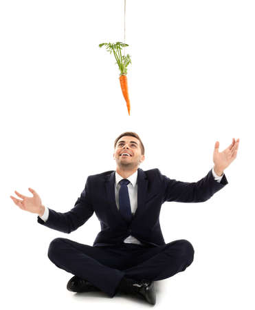 Motivation and goal concept. Young man catching carrot, white background Stock Photo