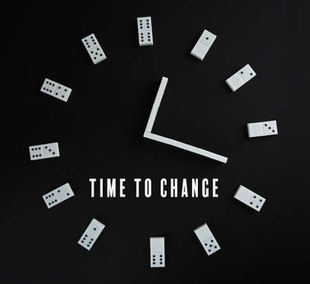 Clock made of dominoes and text TIME TO CHANGE on black background Stock Photo