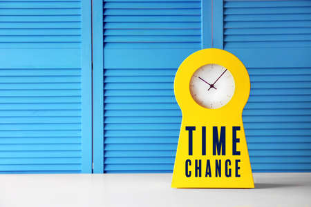 Clock with text TIME CHANGE on blue folding screen background