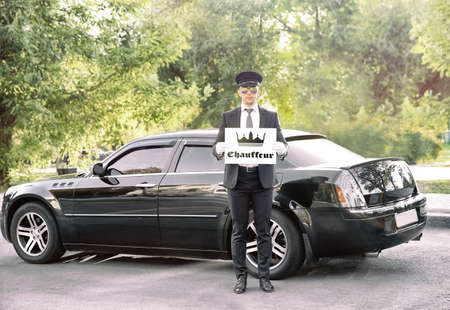 Young man standing with banner CHAUFFEUR near luxury car outdoor Reklamní fotografie - 95153186