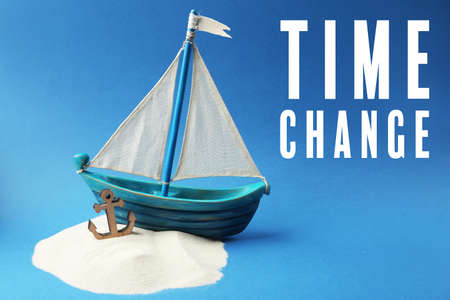 Wooden boat with anchor, sand and text TIME CHANGE on blue background Stock Photo