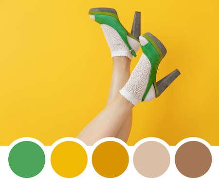黄色の背景にハイヒールの靴を持つ女性。緑色のパレット