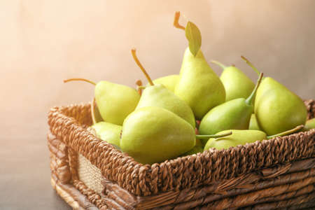 Wicker basket with ripe pears on color background